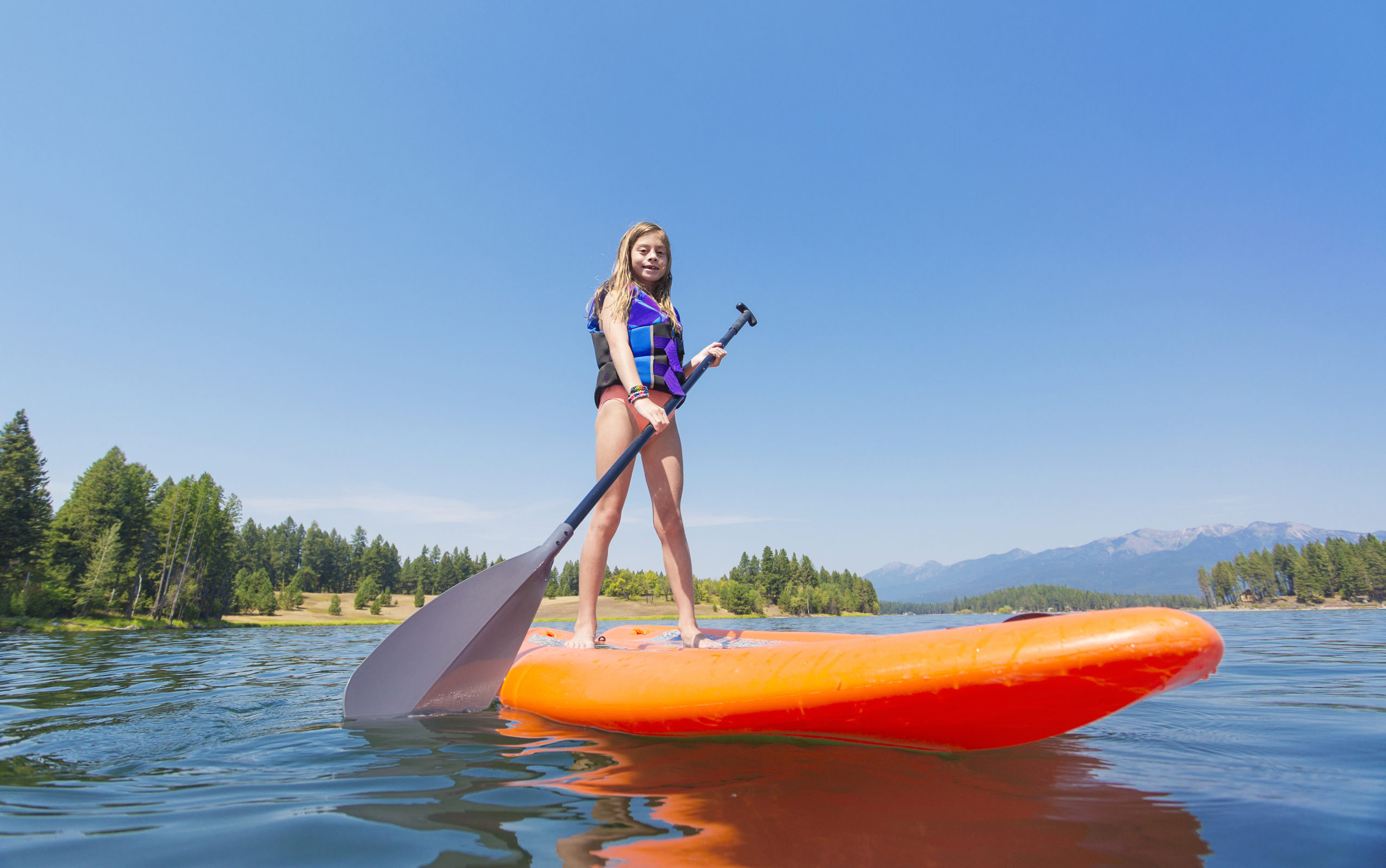 Kid on an inflatable paddleboard on a lake.
