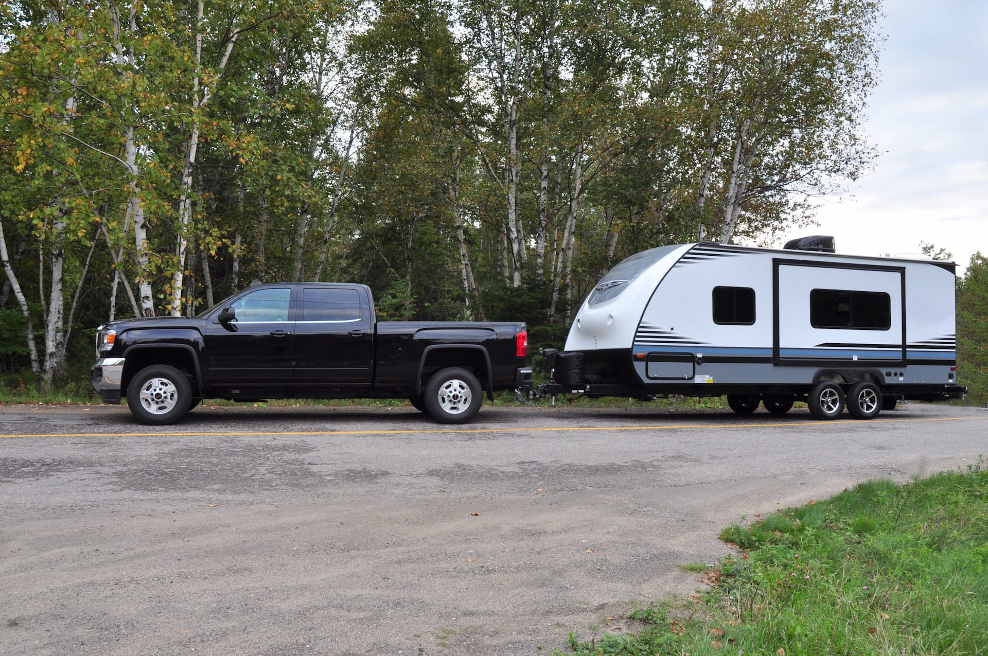 Black GMC truck hitched to a small grey and white travel trailer. The rig is parked on a roughly paved campground road with green deciduous forest in the background.