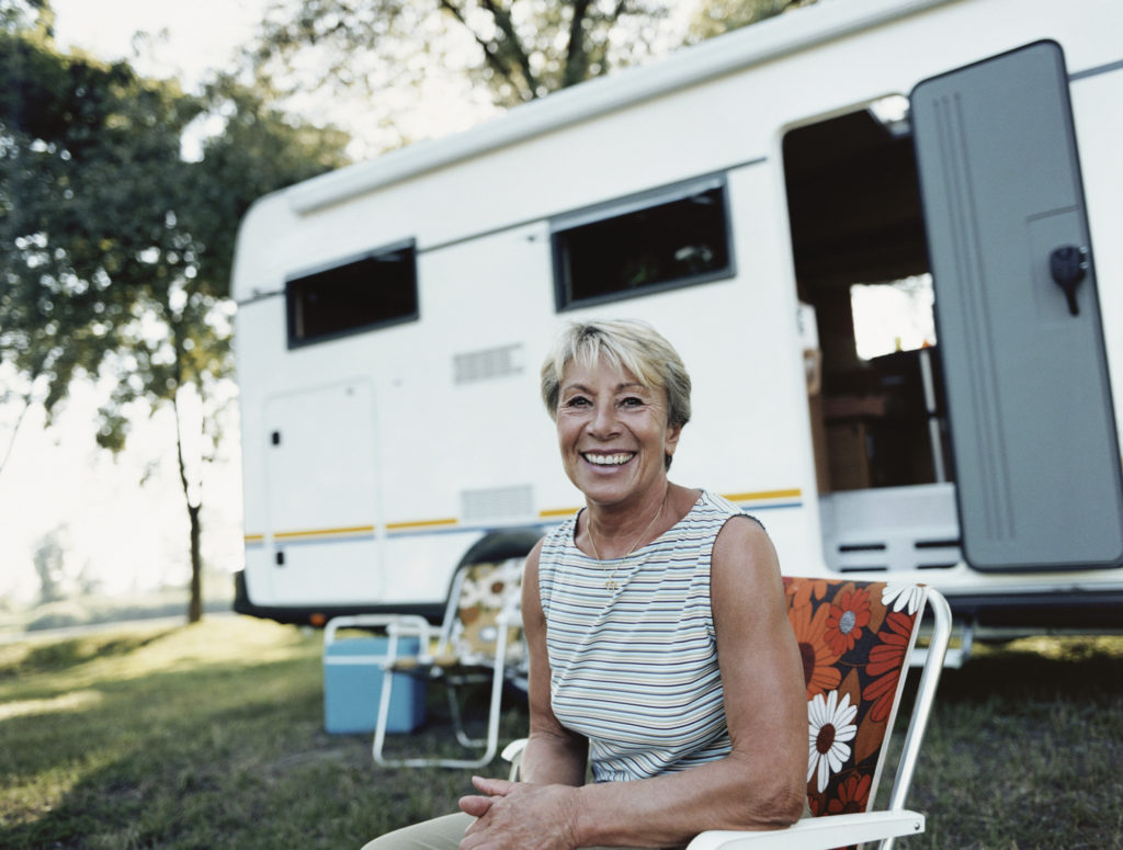 Mature Woman Sits in a Deckchair in Front of a Caravan, Smiling and Looking at the Camera